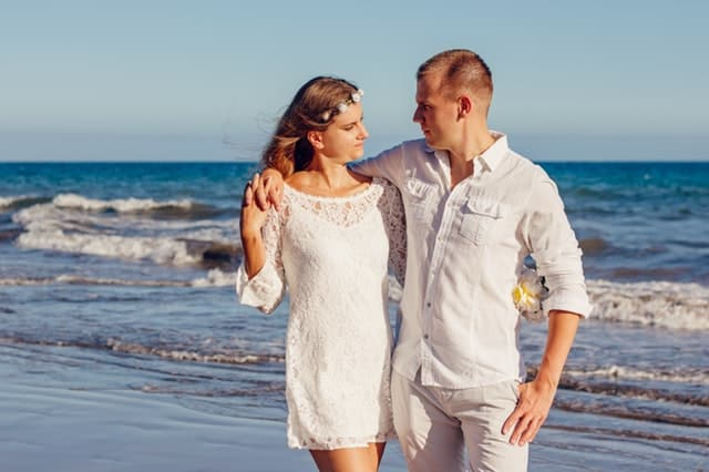 man and woman hugging and walking on the seaside